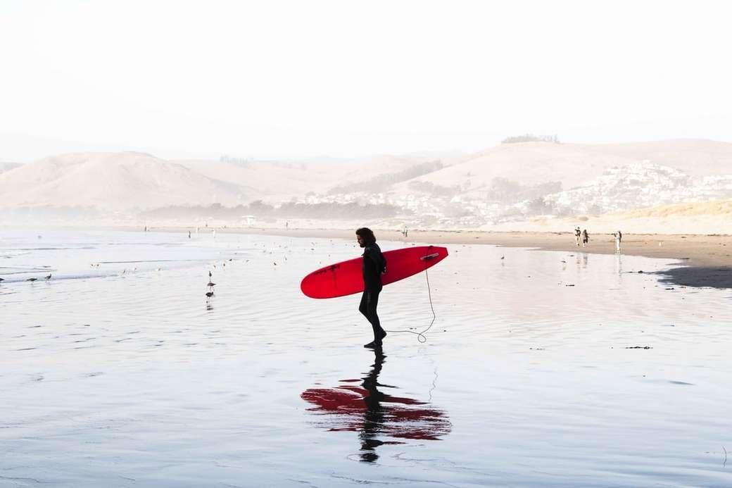 osoba na zbiorniku wodnym przewożąca czerwoną deskę surfingową