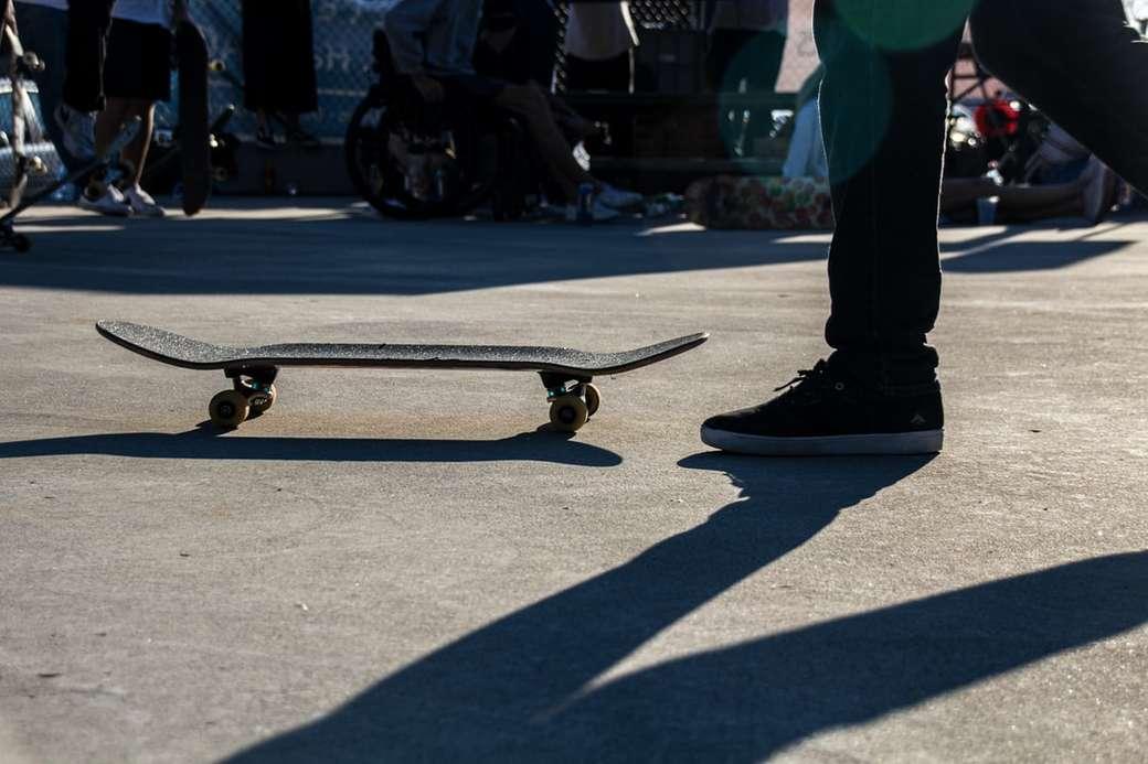 човек, стоящ пред скейтборд онлайн пъзел
