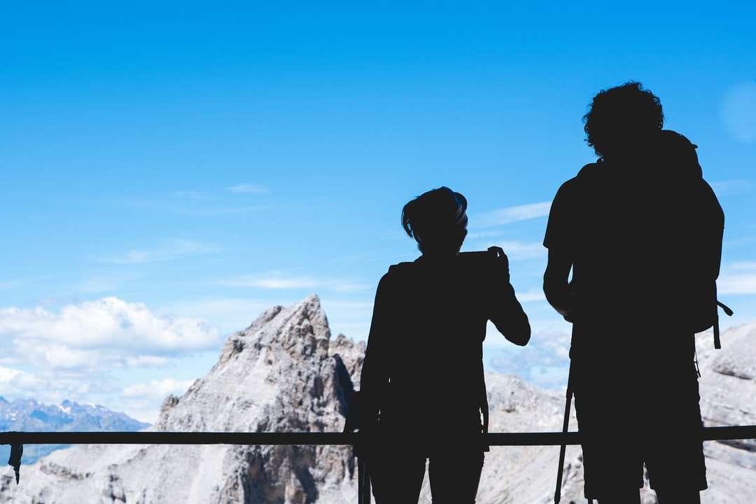 fotografia de silhueta de duas pessoas em pé no topo