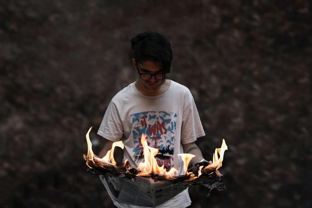 Homem, em, branca, tripulação, pescoço, t-shirt segurando fogo quebra-cabeça