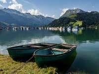 Синя и кафява лодка на зелена трева близо до тялото на водата