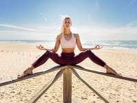 Kaukaska blondynka ćwiczy jogę na plaży